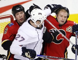 Dustin Penner helps Robyn Regehr to adjust his helmet